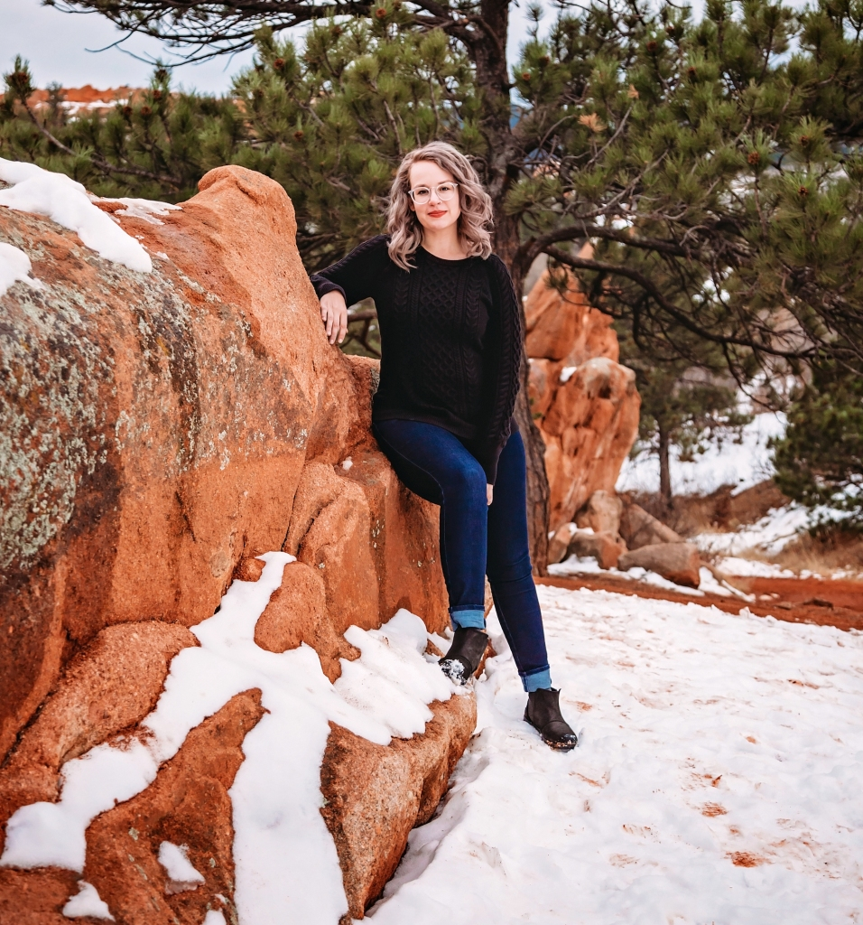 Shelby leans against an outcropping of red rocks. She's wearing jeans, a black sweater, and black books. There's snow on the ground and pine trees in the background.